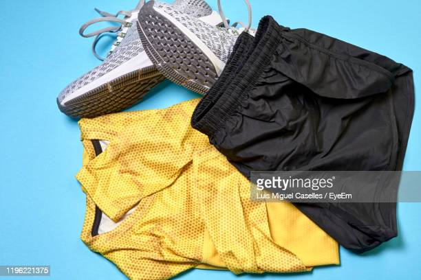 high angle view sports clothes over blue background - black shorts stock pictures, royalty-free photos & images