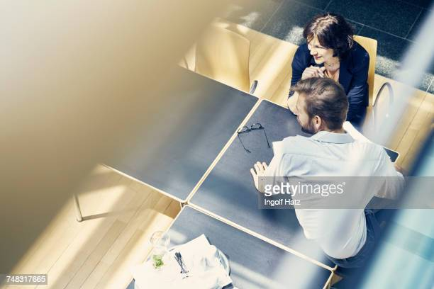 High angle window view of businesswoman and man looking over in office