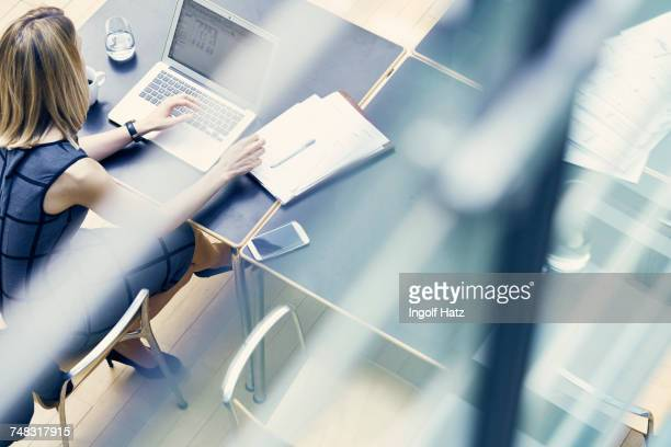 High angle window view of young businesswoman typing on laptop at office desk
