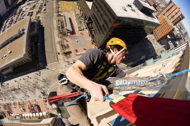 high angle worker dangling from tall building - high up stock pictures, royalty-free photos & images
