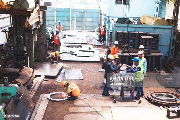 high angler view of a factory in work. - metallic suit stock photos and pictures