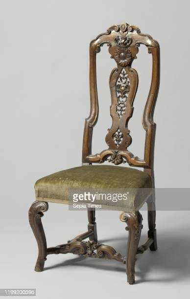 High back walnut chair with carving of Cvolutes and sunflower Angled Sshaped front legs cross with scalloped side sports Upholstered chair made of...