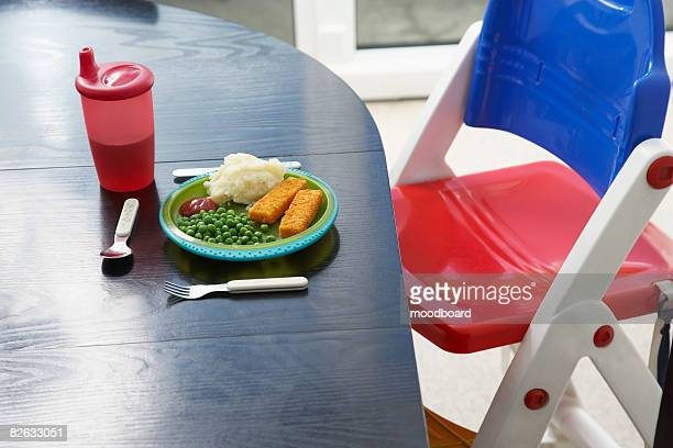 High chair at table with childs dinner, close-up