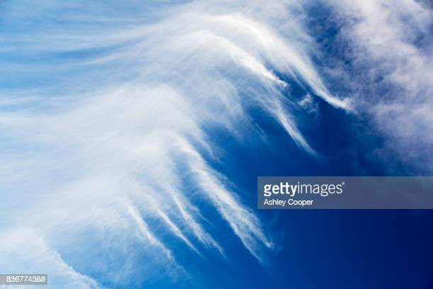 high cirrus cloud, a sign of high winds in the upper atmosphere, over cley, norfolk, uk. - wispy stock photos and pictures