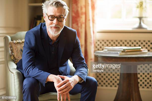 high class mature man portrait at home. - elegantie stockfoto's en -beelden