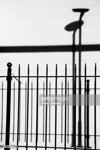 high contrast of metallic railing with street lamp on the back - railings stock pictures, royalty-free photos & images