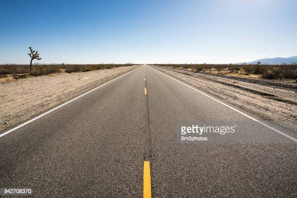 high desert highway road vanishing point - thoroughfare stock photos and pictures