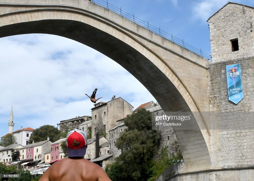 A high diver leaps from a tower built on top of the Old Bridge in Mostar, during the Red Bull Cliff Diving World Series 2017 competition on September 16, 2017. /