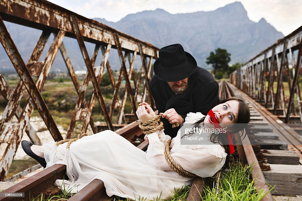 High drama as Victorian villain ties terrified maiden to railtrack! : Stock Photo