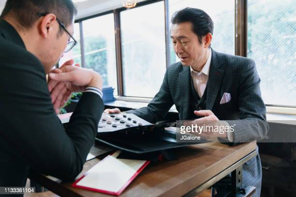 high end tailor talking to a customer - customer focused stock pictures, royalty-free photos & images