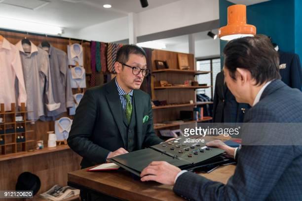 high-end kleermaker in gesprek met een klant - klanten georiënteerd stockfoto's en -beelden
