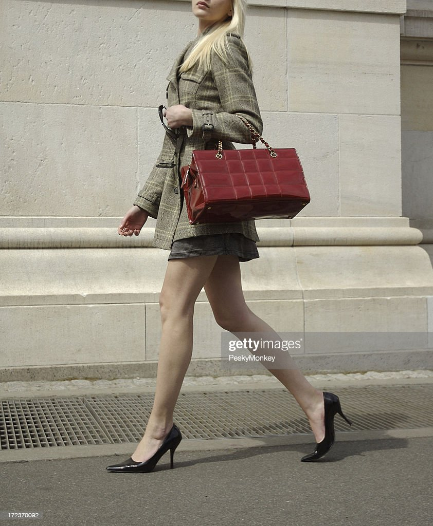 High Fashion Blonde Woman Walks with Shiny Red Bag : Stock Photo