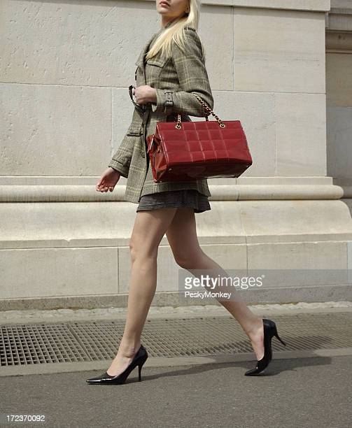 High Fashion Blonde Woman Walks with Shiny Red Bag