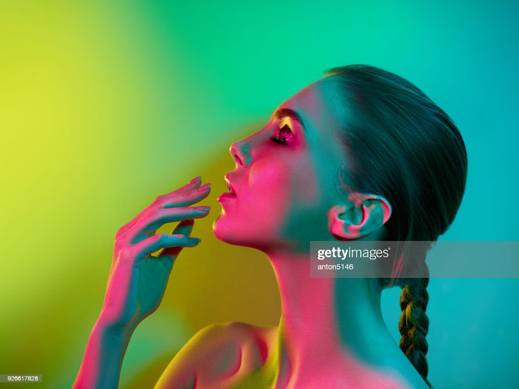 High Fashion model woman in colorful bright lights posing in studio : Stock Photo