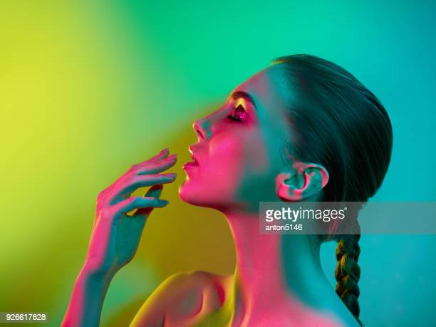 high fashion model woman in colorful bright lights posing in studio - stage make up stock photos and pictures