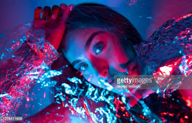 high fashion model woman in colorful bright neon blue and purple lights posing in studio. portrait of beautiful girl with trendy glowing make-up. art design vivid style - nightclub stock pictures, royalty-free photos & images