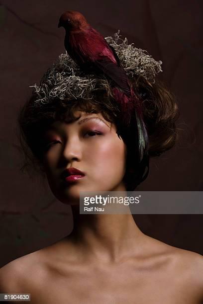 High fashion woman with conceptual bird's nest atop head