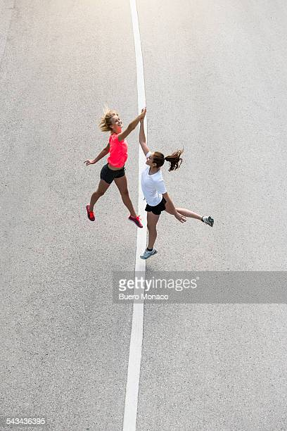 high five of two female runners on street