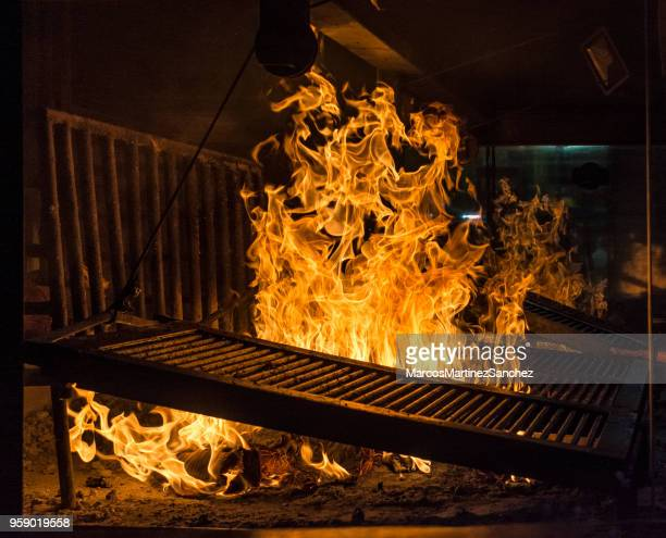 high flame in uruguayan rotisserie, parrilha porteña - smoked food stock photos and pictures