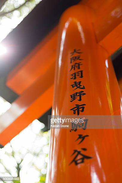 High gloss, orange post of a torii gate with Japanese writing.