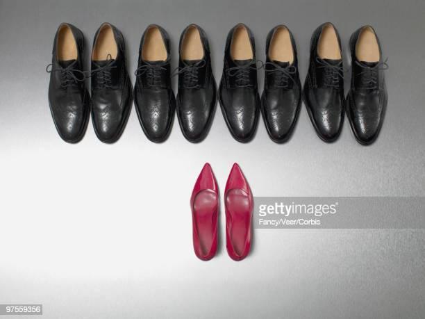 High Heel Shoes Facing Row of Dress Shoes