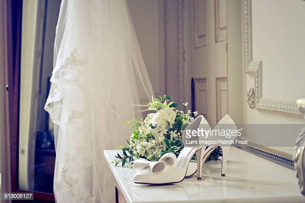 High heels and flower bouquet on mantelpiece, Dorset, England