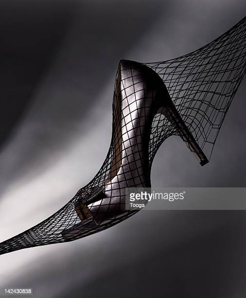 high heels inside black fishnet stockings - fishnet stockings stock pictures, royalty-free photos & images