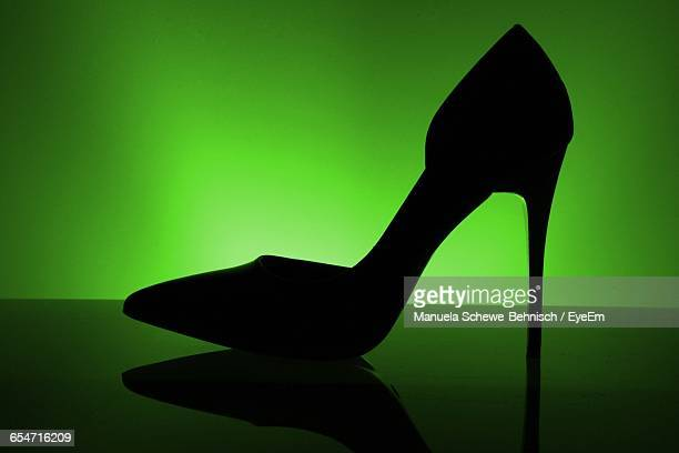 high heels with reflection against green background - stiletto stock pictures, royalty-free photos & images