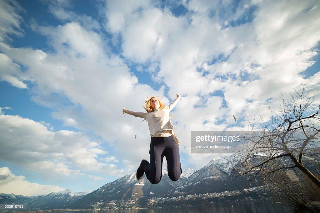 Salto de altura de joven mujer en la naturaleza : Foto de stock