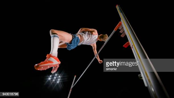 high jumper jumping over bar - high jump stock pictures, royalty-free photos & images