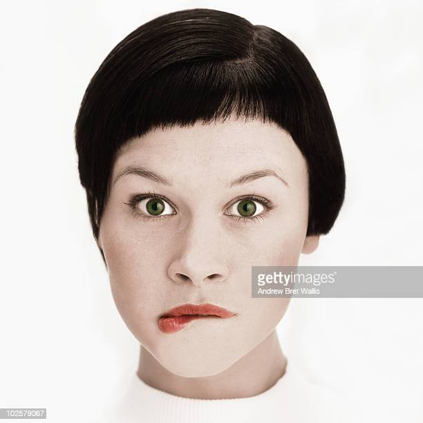 high key portrait of woman chewing her lip - bad bangs stock pictures, royalty-free photos & images