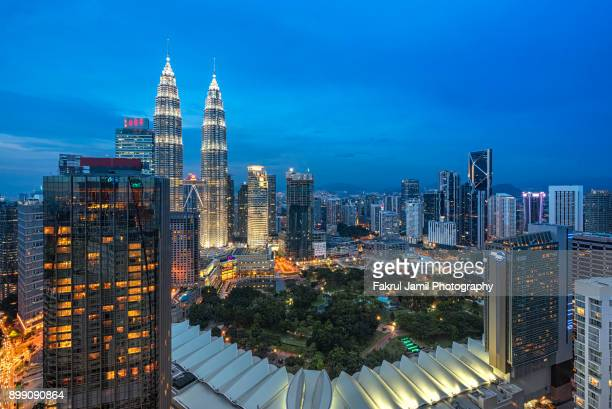 a high pov of kuala lumpur city centre overlooking the petronas twin towers klcc during blue hour - malaysia stock pictures, royalty-free photos & images
