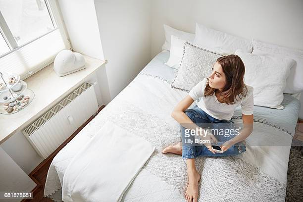High level view of beautiful young woman sitting on bed gazing through window