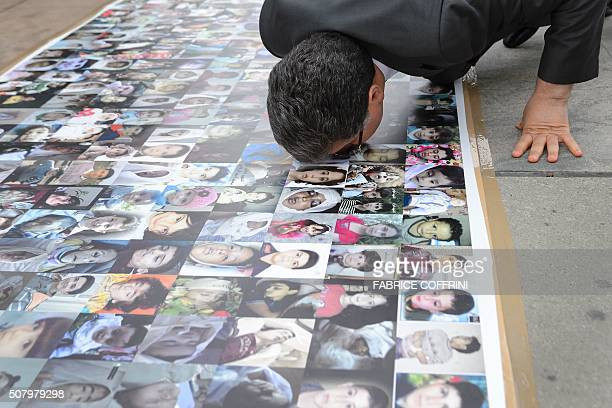 TOPSHOT High Negotiations Committee spokesman Salem alMeslet kisses a banner showing pictures of children killed during the Syrian war at the Places...