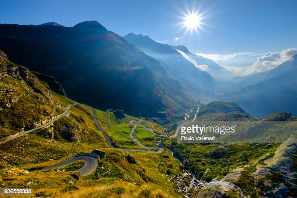high orco valley with the winding road going up towards the nivolet pass. gran paradiso national park, piedmont, italy - valle foto e immagini stock