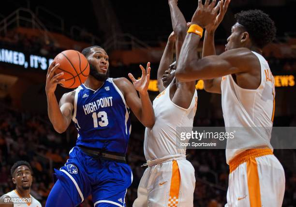 High Point Panthers guard Jahaad Proctor is guarded by Tennessee Volunteers forward Admiral Schofield and forward Kyle Alexander during a game...