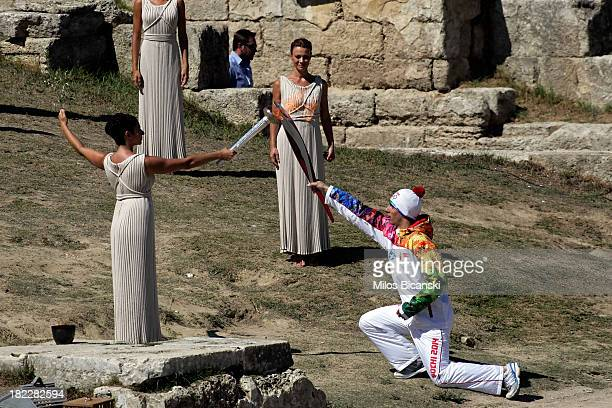 High Priest Ino Menegaki lights the torch of a torchbearer during the lighting ceremony of the Olympic Flame for the Sochi 2014 Winter Olympic Games...