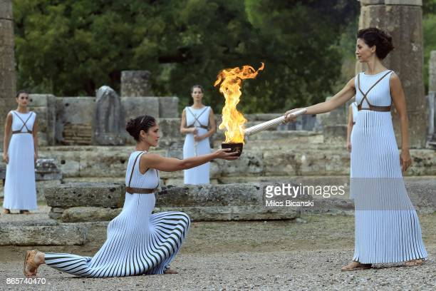 High priestess passes the Olympic flame at the Temple of Hera during a lighting ceremony of the Olympic flame in ancient Olympia on October 24 2017...
