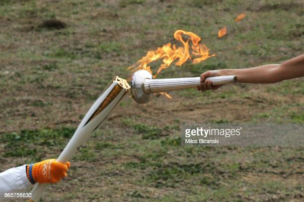 High priestess passes the Olympic flame to the first torch barrier Apostles Aggelis during a lighting ceremony of the Olympic flame in ancient...