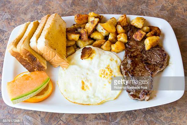 High protein breakfast plate Sirloin stake and fried eggs Sides dishes and garnish include potatoes cantaloupe orange slice with toasts socked in...