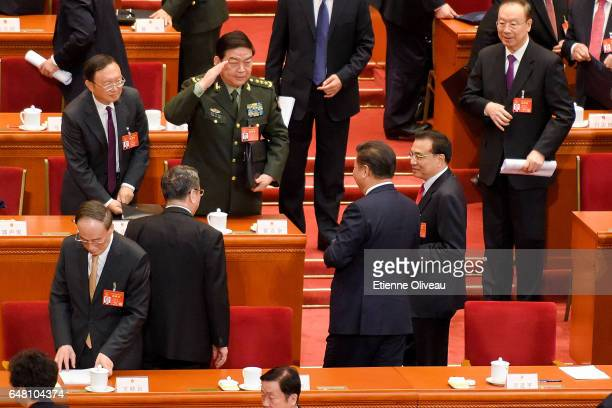 A high rank military officer gives a military salute to Chinese President Xi Jinping and Premier Li Keqiang after the opening session of the National...