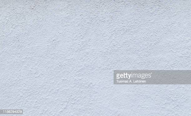 high resolution full frame background of a rough plastered concrete wall in light blue or white color. - プラスター ストックフォトと画像