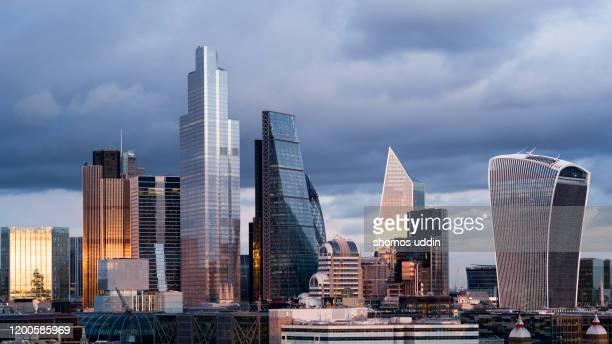 high rise financial buildings against moody sky - ロンドン市 ストックフォトと画像