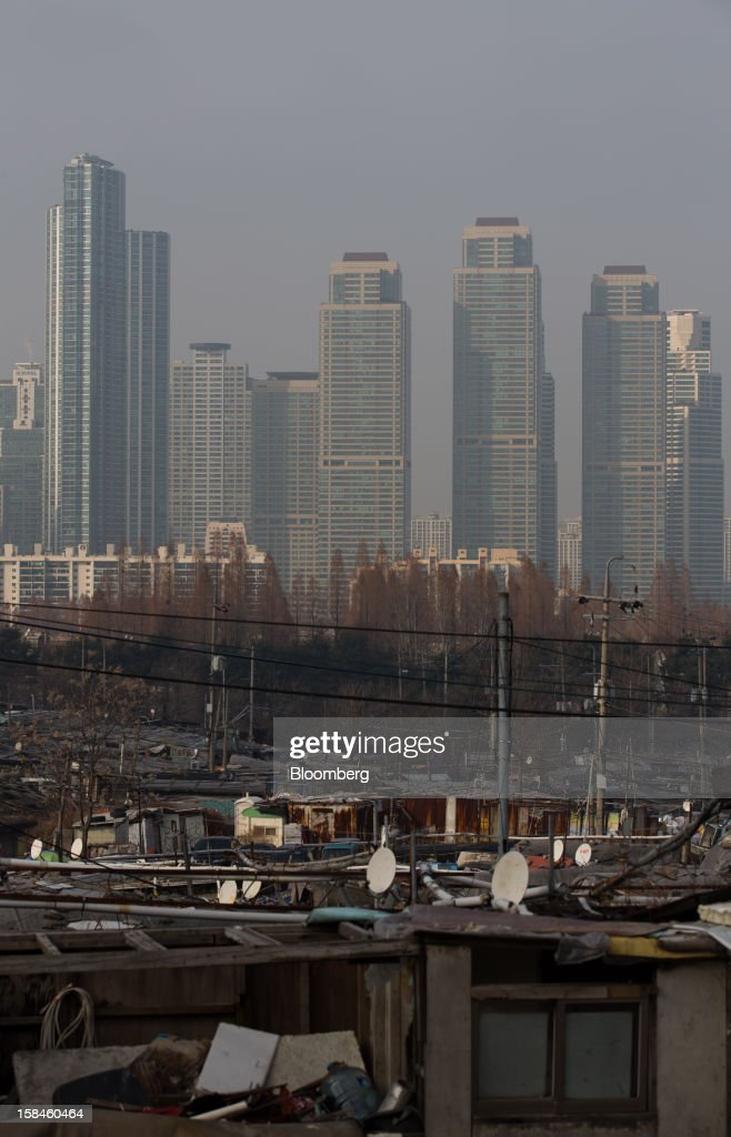 High rise residential buildings tower over Guryong village, foreground, in the Gangnam district of Seoul, South Korea, on Sunday, Dec. 16, 2012. South Koreans vote on Dec. 19 to replace President Lee Myung Bak, whose five-year term ends in February. Photographer: SeongJoon Cho/Bloomberg via Getty Images