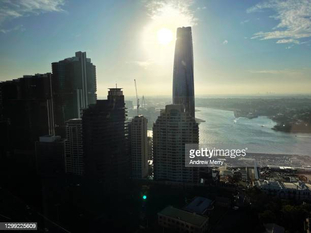 high rise tall buildings, skyscrapers in silhouette, backlit by the sun - darling harbour stock pictures, royalty-free photos & images
