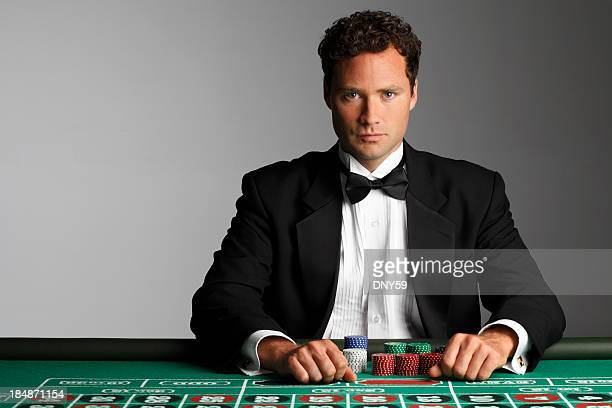 High roller sitting at roulette table with his gambling chips