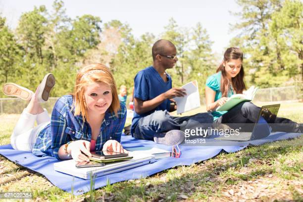High school age friends studying, hanging out at park.