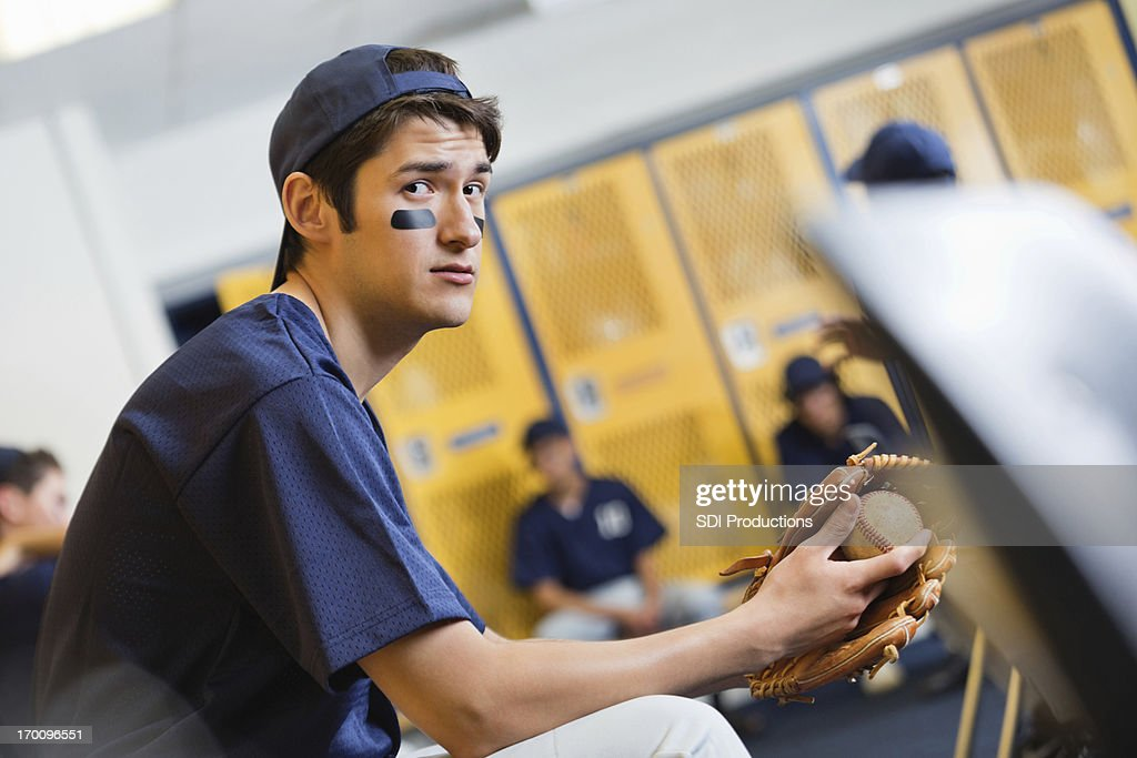 High School Baseball Player Sitting On Bench In Locker Room Stock Photo