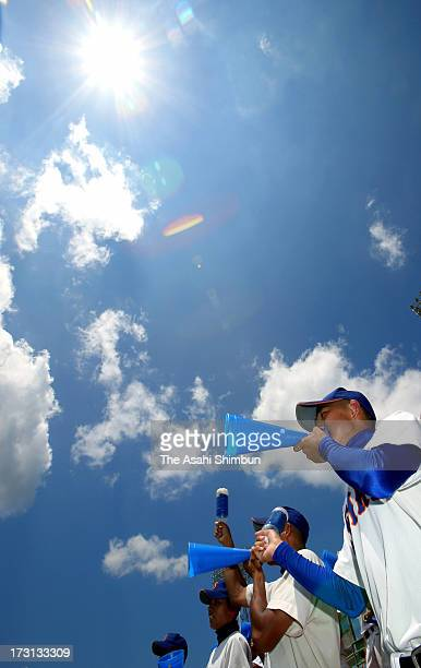 High school baseball players cheer their team on a stand under a strong sunshine as the Japan Meteorological Agency announces that rainy season ends...