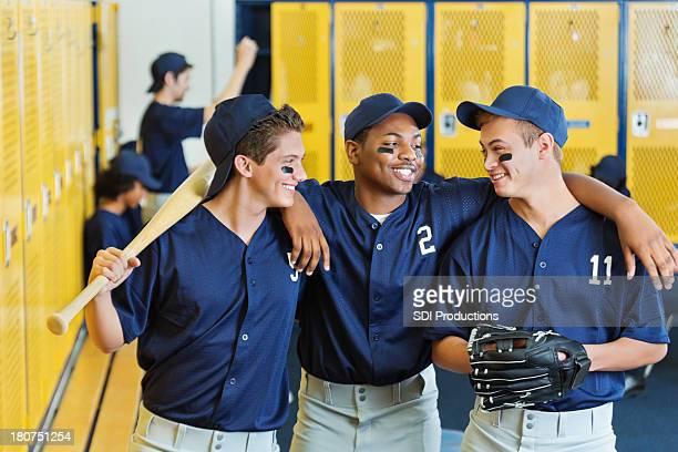 High school baseball team together in locker room after game